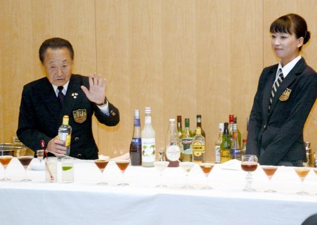 秋山徳蔵のレシピを基にカクテルを再現する嶋田常任顧問(左)=19日、福井県立図書館