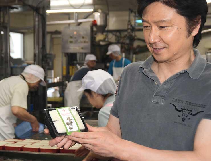 金賞を受賞した豆腐を手にする富成さん