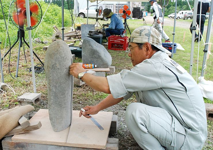 信濃川の石で制作を始めた参加者=20日、十日町市の「結いの里」