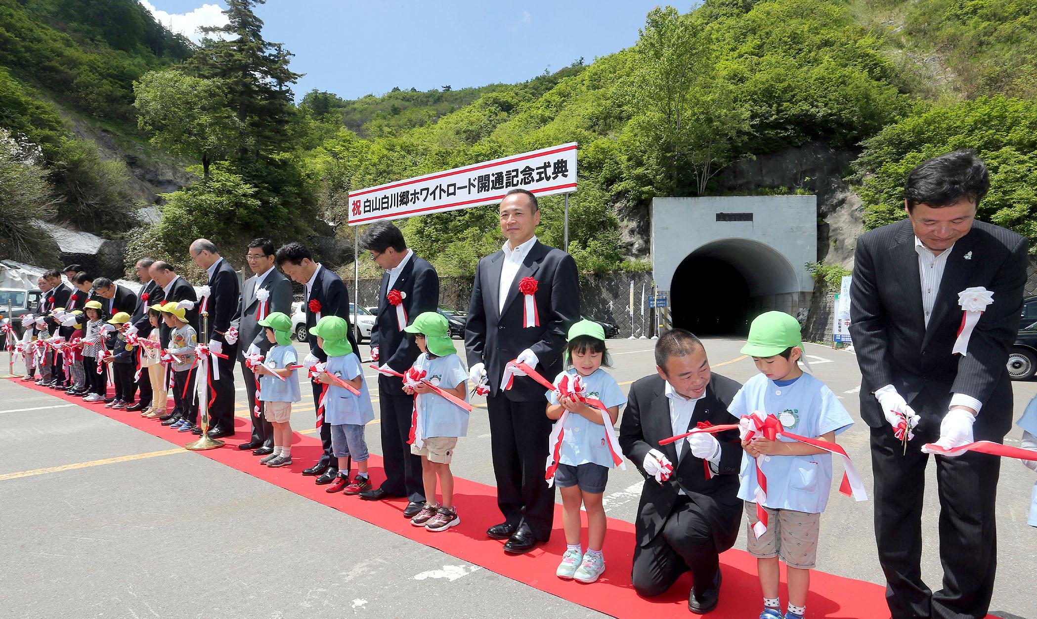 全線開通を祝いテープカットする石川県と岐阜県の関係者=25日午前10時22分、三方岩駐車場