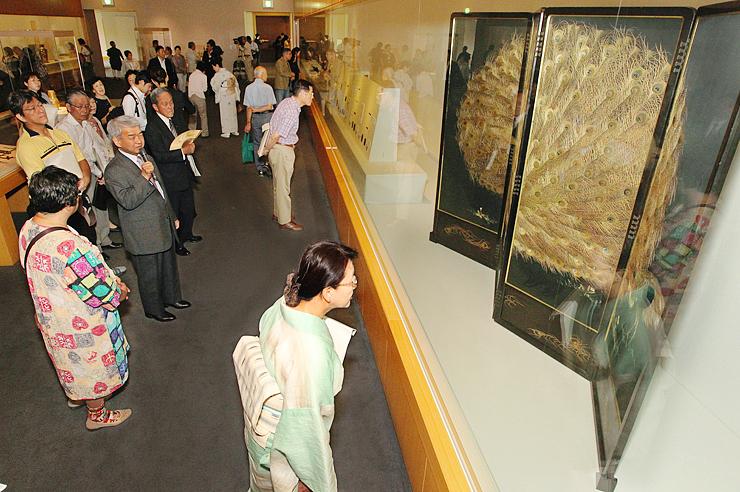 マイクを手にした村田館長(中央左)の解説を聞きながら超絶技巧の工芸品に見入る来場者=県水墨美術館