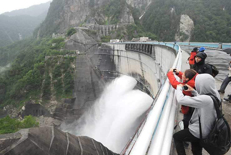 黒部ダムで始まった観光放水を楽しむ観光客たち=26日、富山県立山町