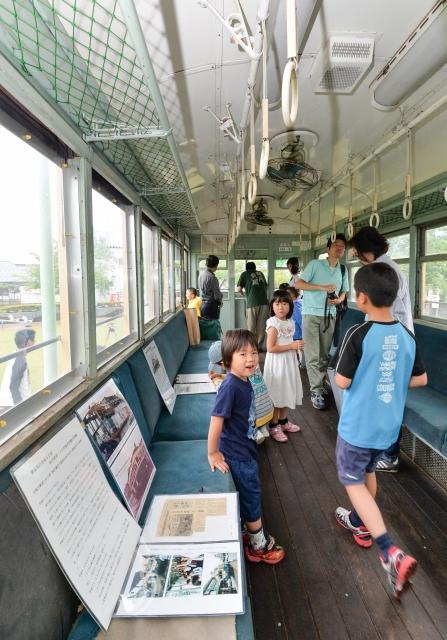 公開された震災電車の中を見学する親子連れら=27日、福井市下馬3丁目の下馬中央公園