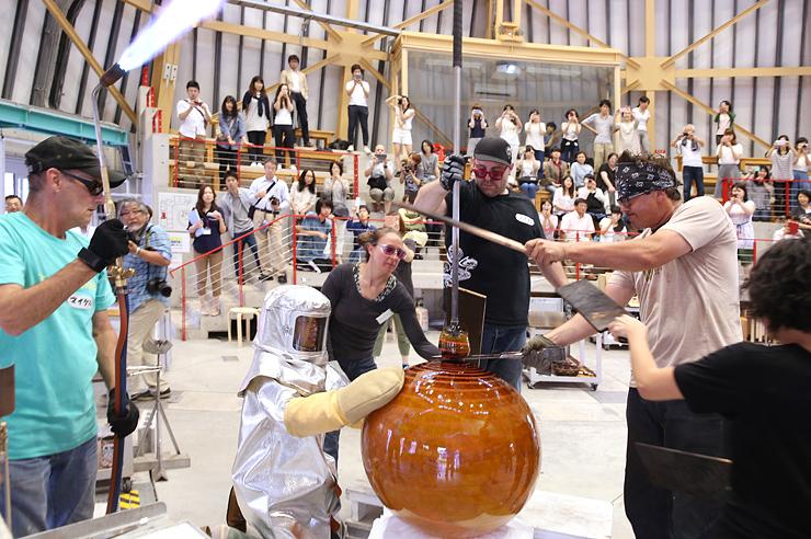 パイプの先に付いたガラスをテーブルに当てながら形を整えるチフーリ・スタジオのスタッフら=富山市古沢の富山ガラス工房第2工房