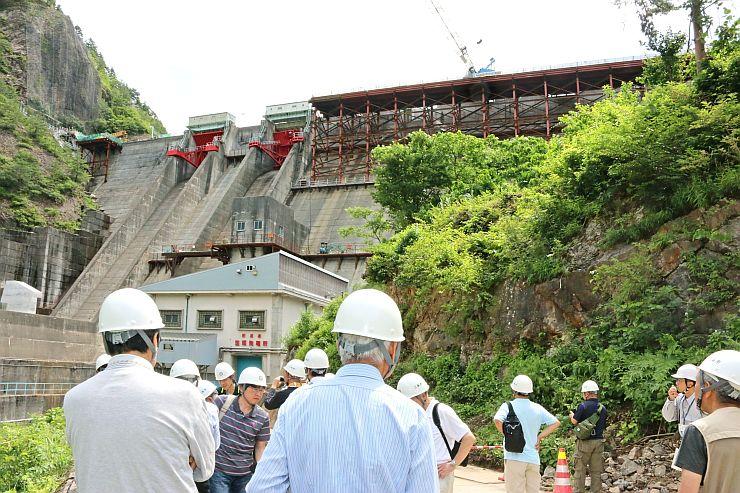かさ上げ工事中の笠堀ダムを見学するツアーの参加者=27日、三条市