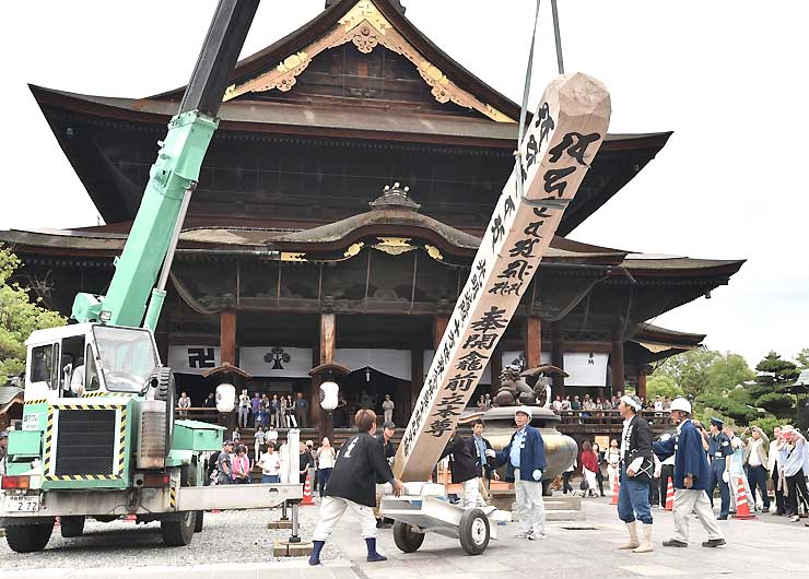 法要の後、クレーン車で横倒しにされる回向柱=30日午後1時25分、長野市の善光寺