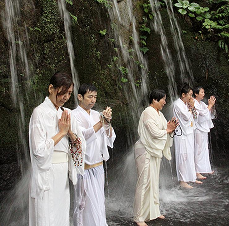 六本滝に打たれる信者たち=上市町の大岩山日石寺