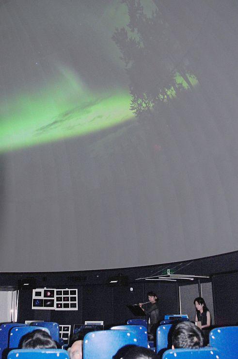オーロラの写真が投影される中、天体にまつわる曲が演奏されたイベント=28日、柏崎市