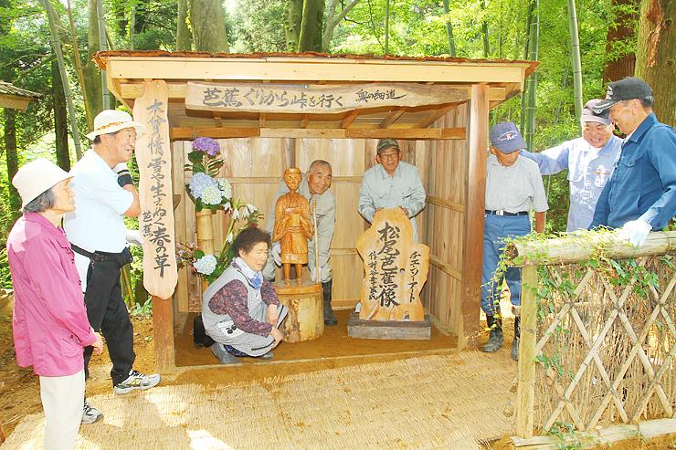 旧北陸街道沿いに松尾芭蕉像(中央)を設置し、喜ぶ会員ら