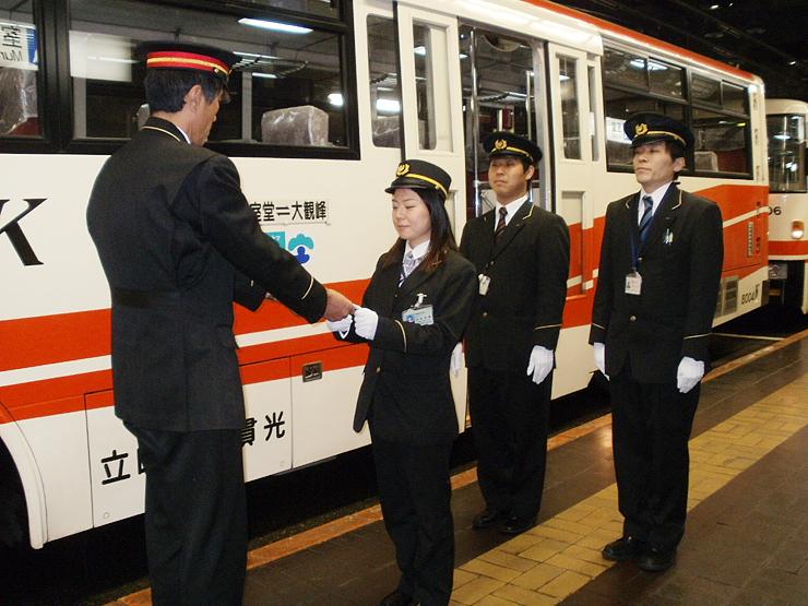 上司からトロリーバスの運転免許を受け取る山本さん(中央)=2日、立山・室堂駅