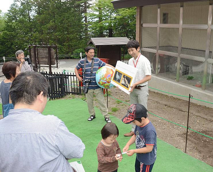 4日に公開を始めたスバールバルライチョウの飼育舎(右奥)前で開いた見学会=4日、大町市