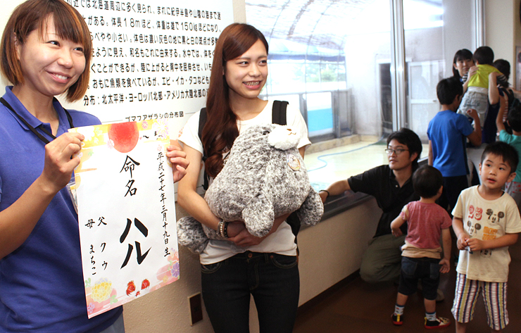 記念品のぬいぐるみを手に、名前に込めた思いを語る濱谷さん(中央)=魚津水族館