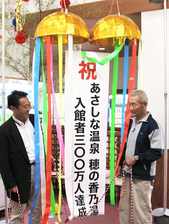 柳田市長とくす玉を割った300万人目の来場者の加藤さん(右)