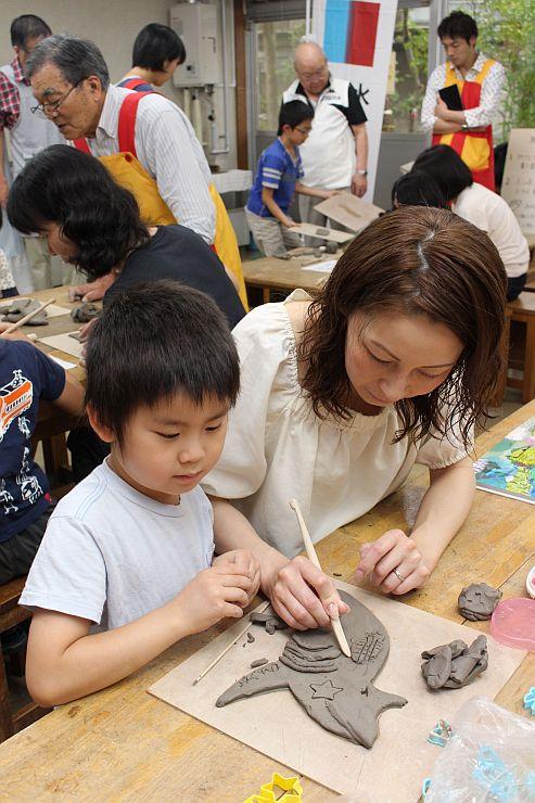 海の生き物をかたどった陶板を作る子どもたち=4日、新潟市中央区