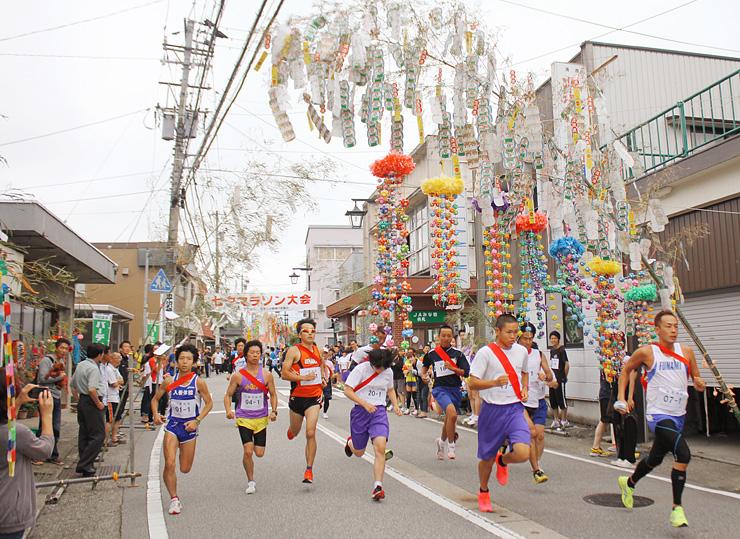 七夕飾りに彩られた通りを駆け抜けるマラソン大会参加者=入善町舟見