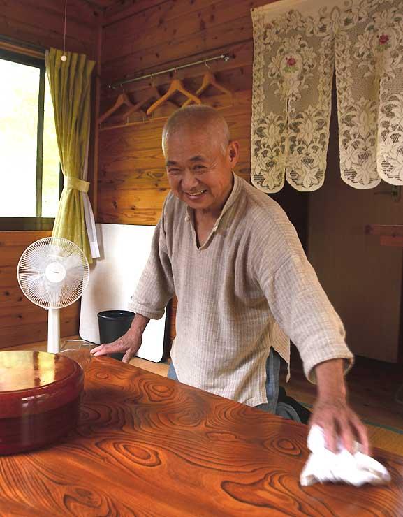 ログハウスの営業再開を目指して室内の掃除などをする吉田さん