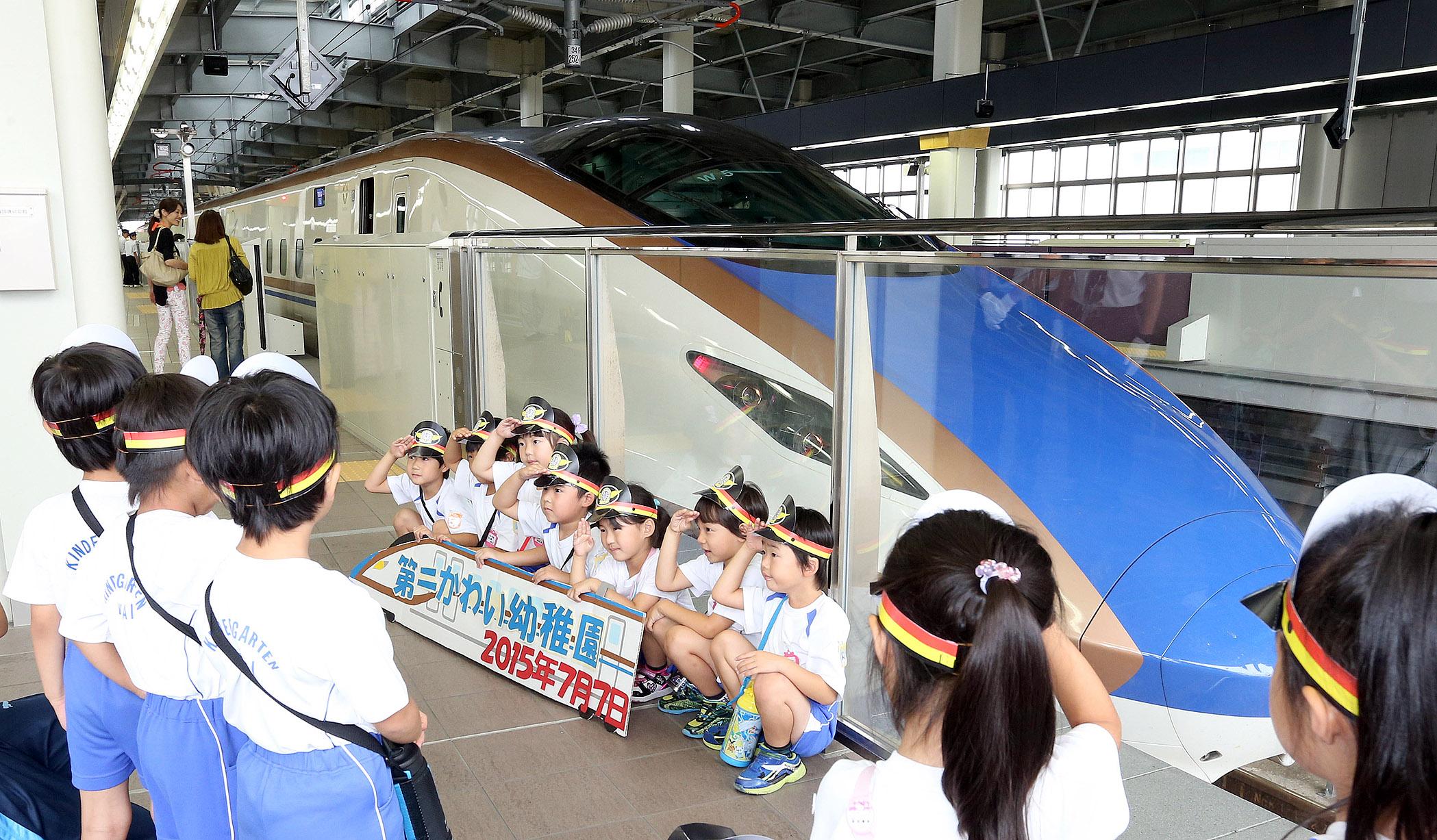 新幹線車両と記念撮影する園児=JR金沢駅
