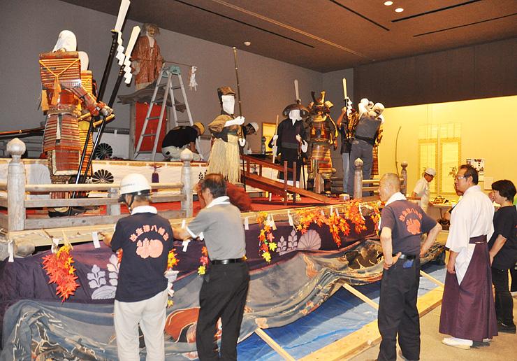 射水市新湊博物館の展示室内で祭壇を組み上げる大伴宮司(右から2人目)と放生津八幡宮文化財保存会のメンバー
