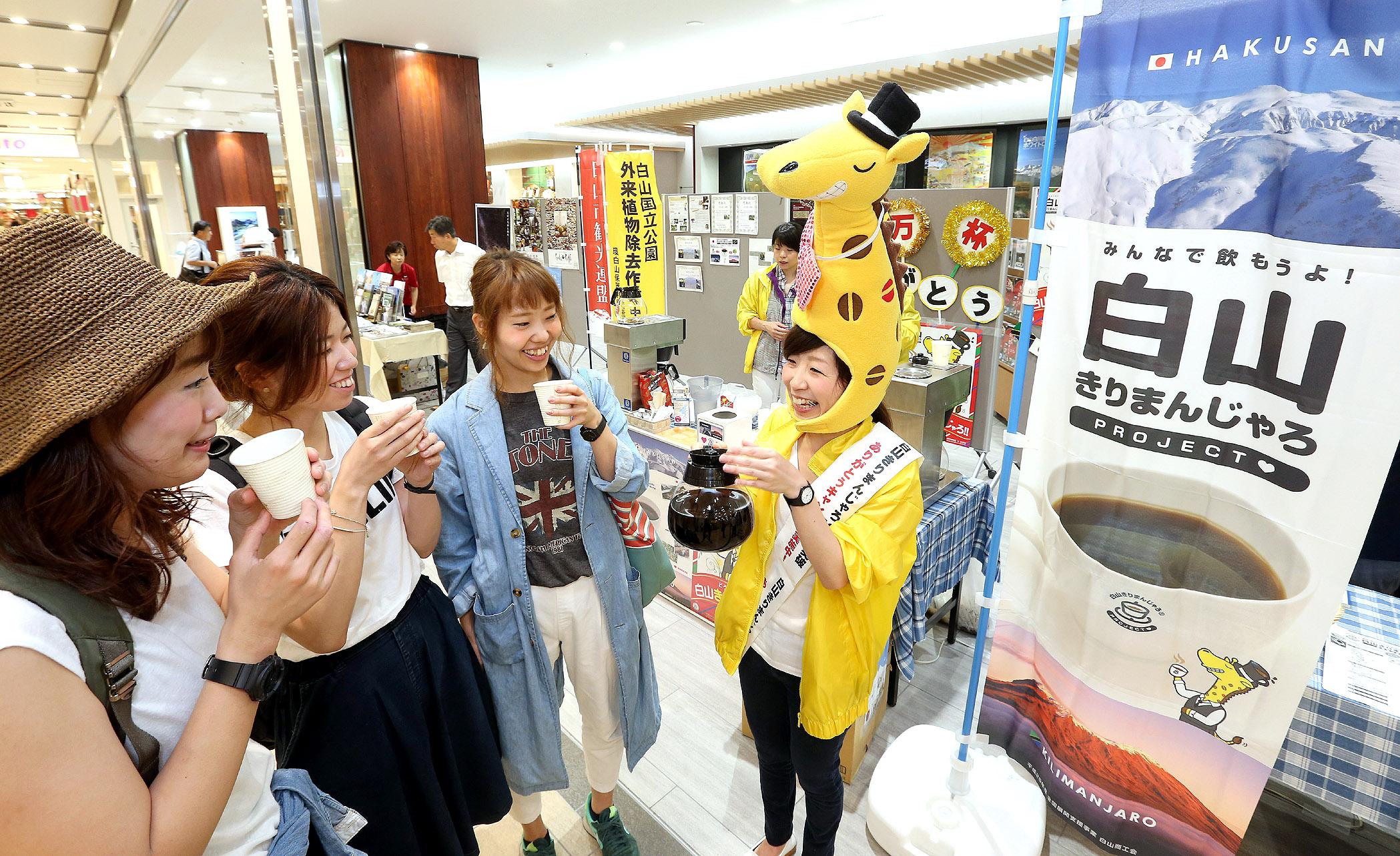 コーヒーを味わう来場者=JR金沢駅構内の観光案内所