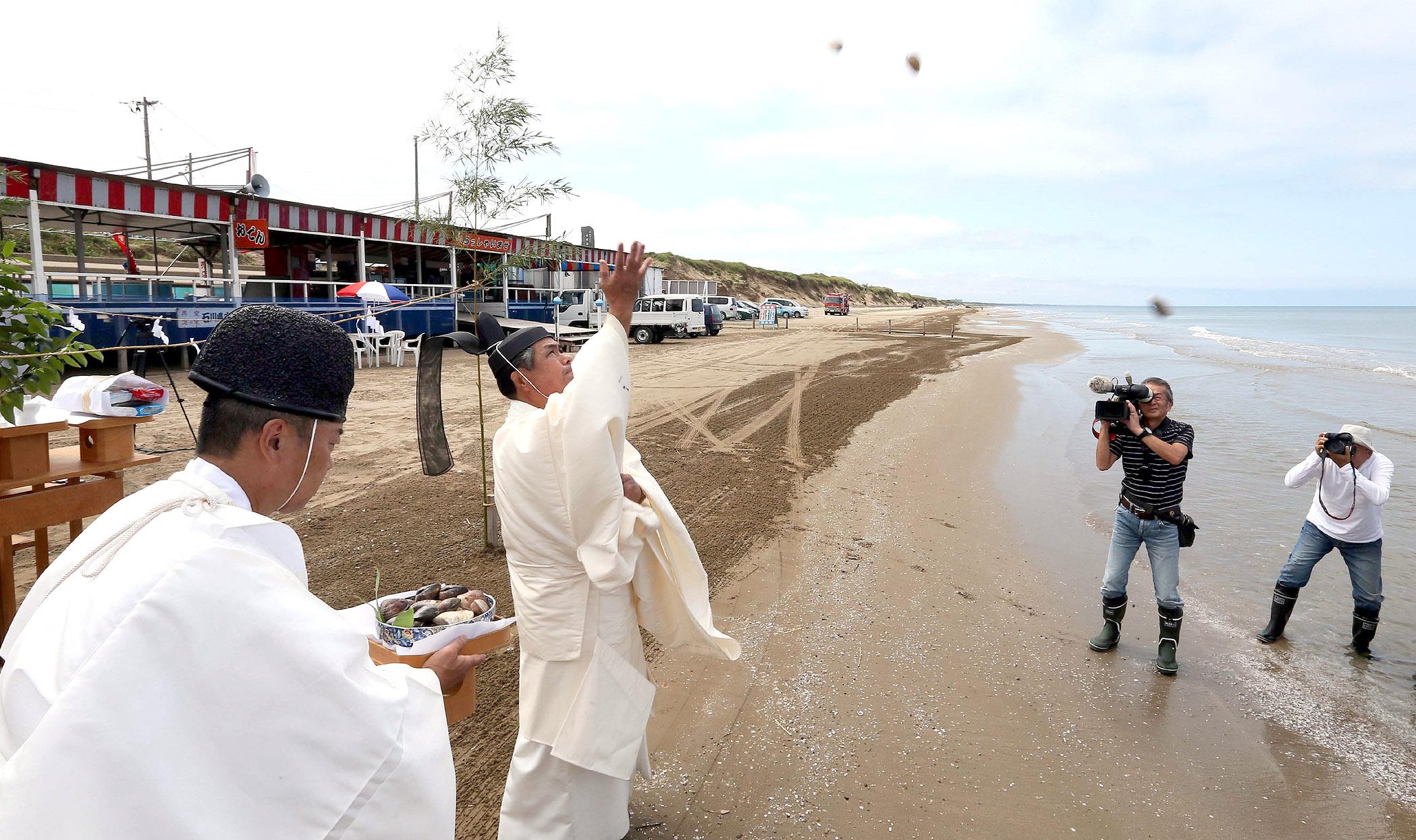 夏のにぎわいと安全を願ってハマグリを投げ入れる神職=10日午前10時12分、羽咋市の千里浜海水浴場