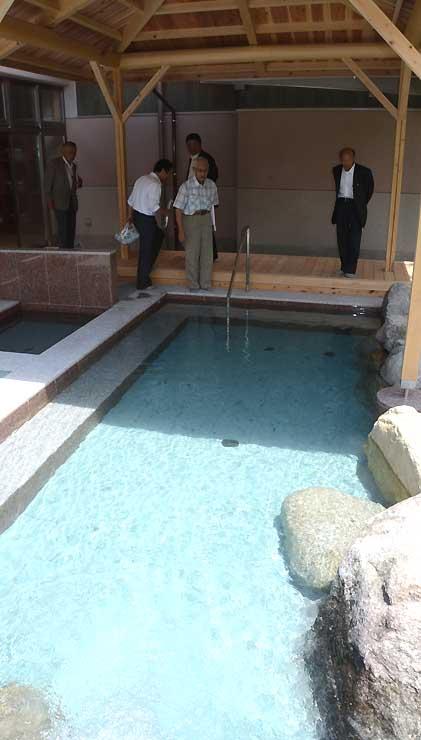 建て替えで新しくなった露天風呂を見学する参加者たち