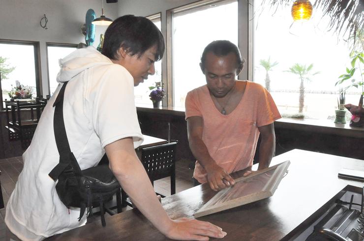 来店客(左)に波の写真を見せながら説明する宮田オーナー=高岡市太田