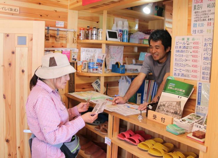 宮下さん(右)から記念ポストカードを受け取る宿泊者