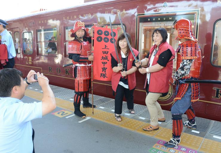 「ろくもん」の前で、「上田城甲冑隊」のメンバーと記念写真に納まる観光客