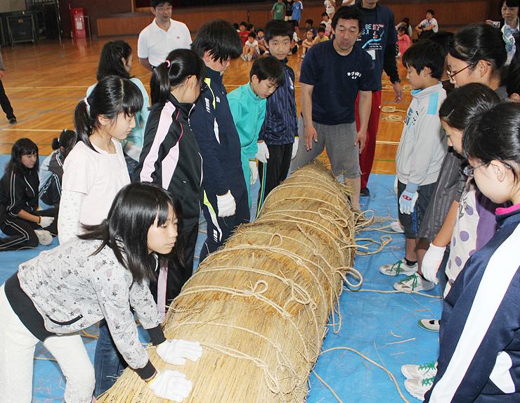 力を合わせてわらを巻き、ネブタを作る児童=滑川市寺家小学校
