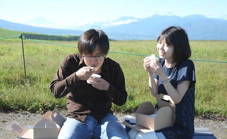 霧ケ峰で朝食を楽しむ中野賢司さん(左)と妻由美子さん。富士山(左奥)も見えた=14日午前7時40分ごろ