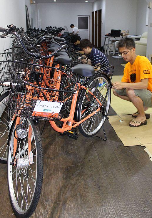 レンタサイクルとして運用する新車両に、専用のシールを貼るボランティアら=13日、新潟市中央区