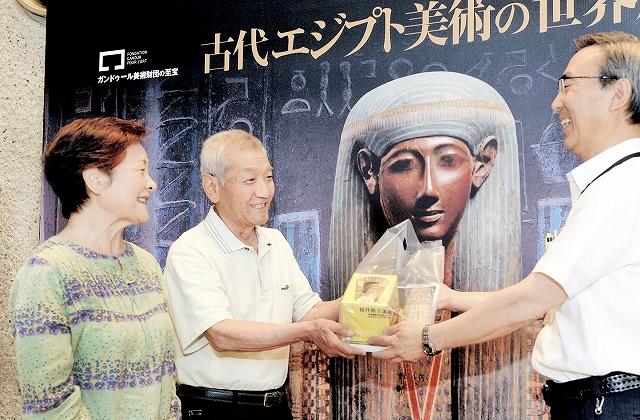 1万人目の来場者となり記念品を受け取る野路清さん(左から2人目)と孝子さん=17日、福井市の県立美術館