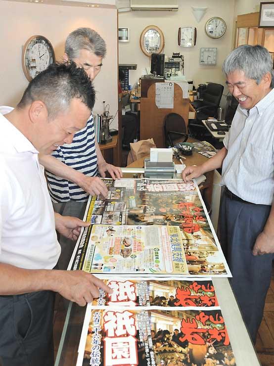 完成した岩村田祇園祭のチラシを見て出来具合に笑みがこぼれる実行委員たち