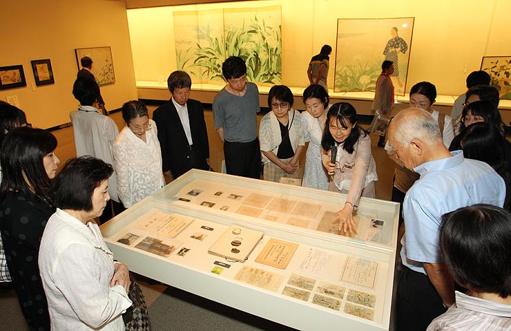 学芸員の解説を聞きながら、戦争で亡くなった画学生の遺品や遺作に見入る来場者=県立近代美術館