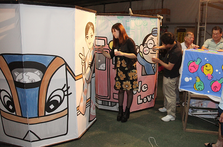 北陸新幹線開業を祝う大あんどんに描かれた自身のイラストに色を塗る林道美有紀さん(写真中央)ら