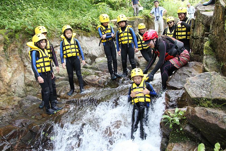 岩場の急な流れを滑り降りる児童たち