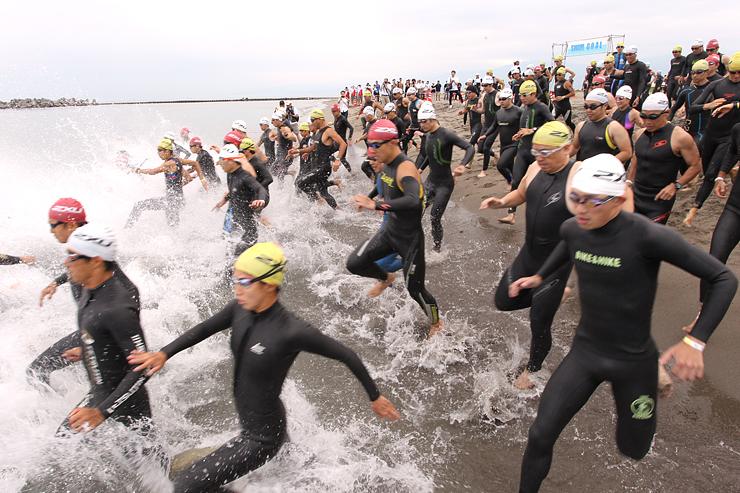 15年ぶりの復活開催となった「いきいき富山トライアスロン2015」。スタート 勢いよく海に飛び込む選手たち=富山市の岩瀬浜