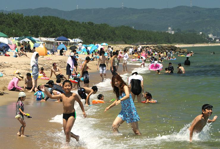 好天となった3連休最終日、浜辺に繰り出し海水浴を楽しんむは大勢の家族連れら=氷見市の島尾海水浴場