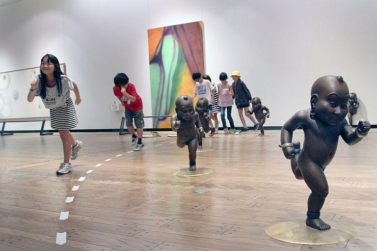 彫刻の動きをまねして作品を楽しむ子どもたち=長岡市