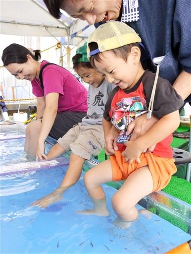 ドクターフィッシュが足の皮膚をついばむ感触を楽しむ子ども=22日、坂井市三国町の越前松島水族館