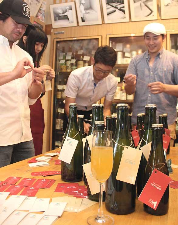 伊那谷産のリンゴのシードルとイチゴのスパークリングワインにラベルを付ける渡辺さん(右端)ら