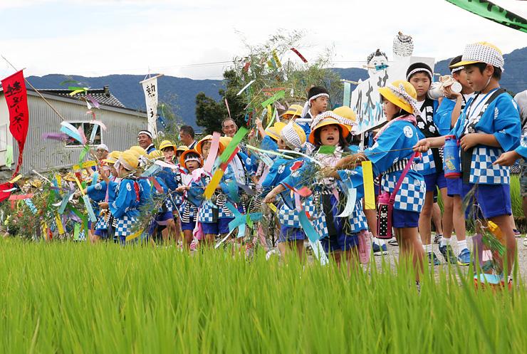 田んぼに向かい、「ねつおくるばーい」とササ竹を振る児童たち=南砺市荒木