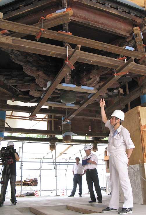 揚屋工法で持ち上げた輪蔵下で修理状況を説明する担当者