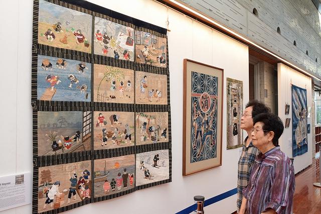 昔の田舎の風景や漁業の様子を描いた布絵が並ぶ「若狭の海に生きる」出版記念展=25日、美浜町生涯学習センターなびあす