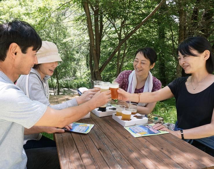 上高地の豊かな緑の中、クラフトビールで乾杯する来場者たち