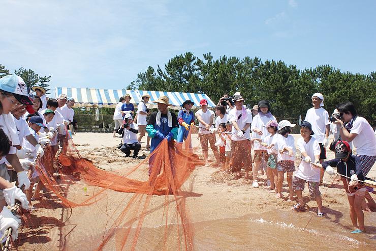地引き網を体験する親子連れら=島尾海岸