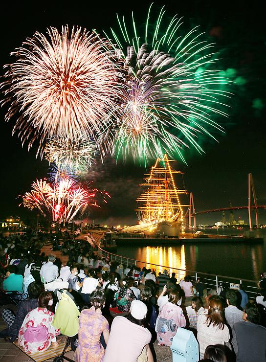 海王丸と新湊大橋(右)の上空を鮮やかに彩る大輪の花火=海王丸パーク(多重露光撮影)