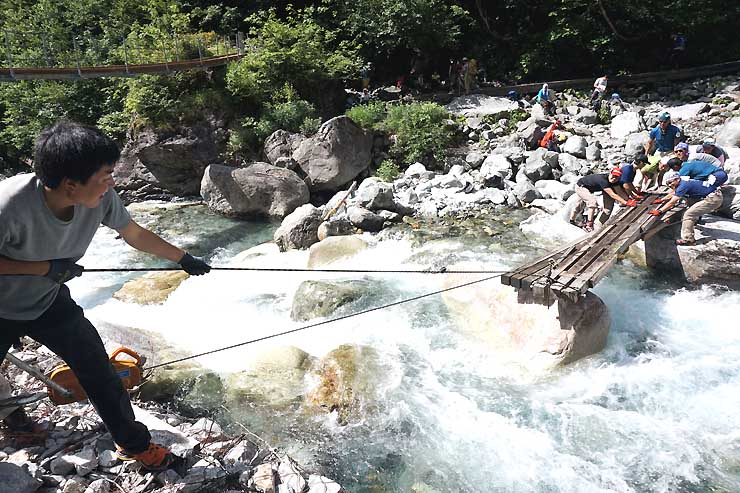 本谷橋(左上)の上流に木製の仮橋を設置する山小屋関係者ら