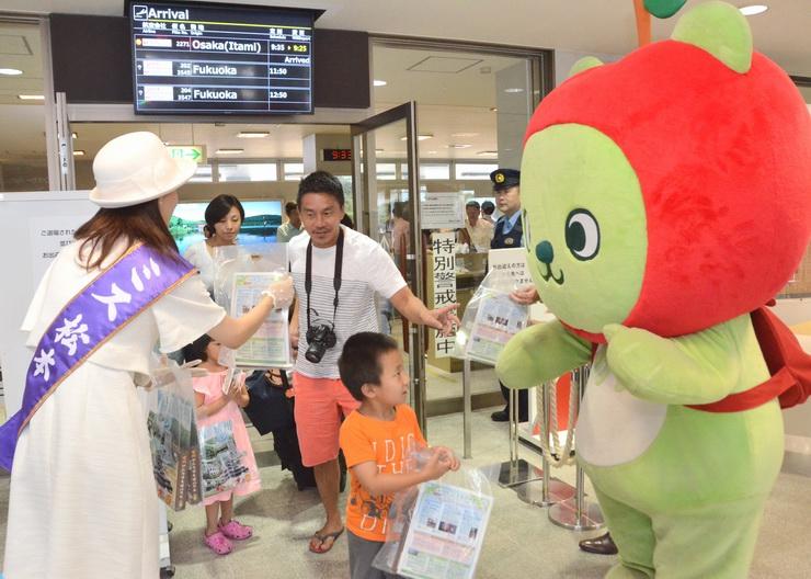 県営松本空港に到着した大阪便の第1便の乗客に信州の特産品を渡すアルクマら=1日