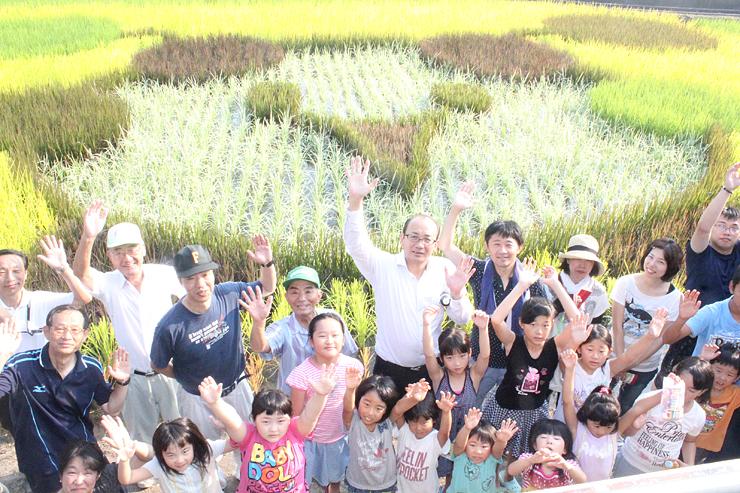 田んぼに浮かび上がった「NANTOくん」の前で万歳をして祝う住民ら=南砺市高堀